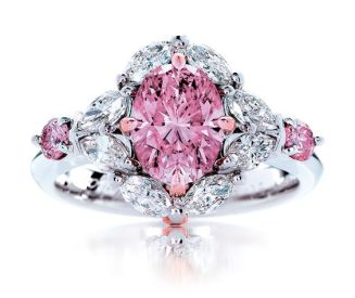 Pink diamond ring with smaller pink stones at cardinal points and diamond like stones around