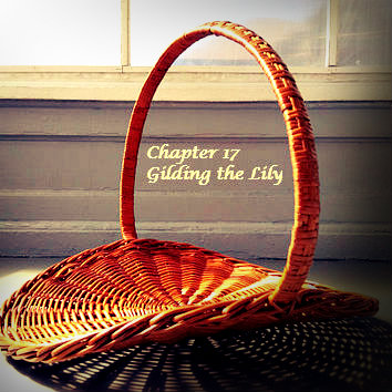 "A slightly curved, wicker flower basket sitting by a window in sunlight with a shadow underneath. Within the circle of the handle are the words ""Chapter 17 Gilding the Lily."""